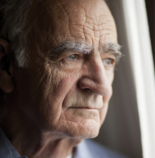 Elderly gentleman gazing out a window