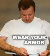 Wear Your Armor (picture of a man putting on body armor)