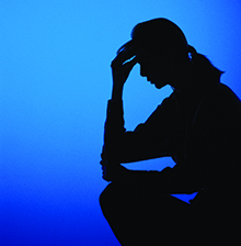 Silhouette of a person holding their head