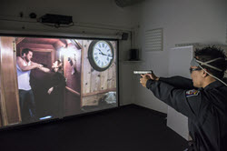 Officer aiming his firearm at a simulation showing a man holding a woman at gunpoint
