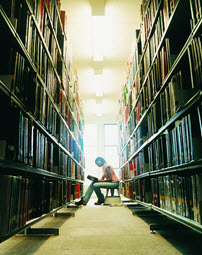 Young woman reading in library stack