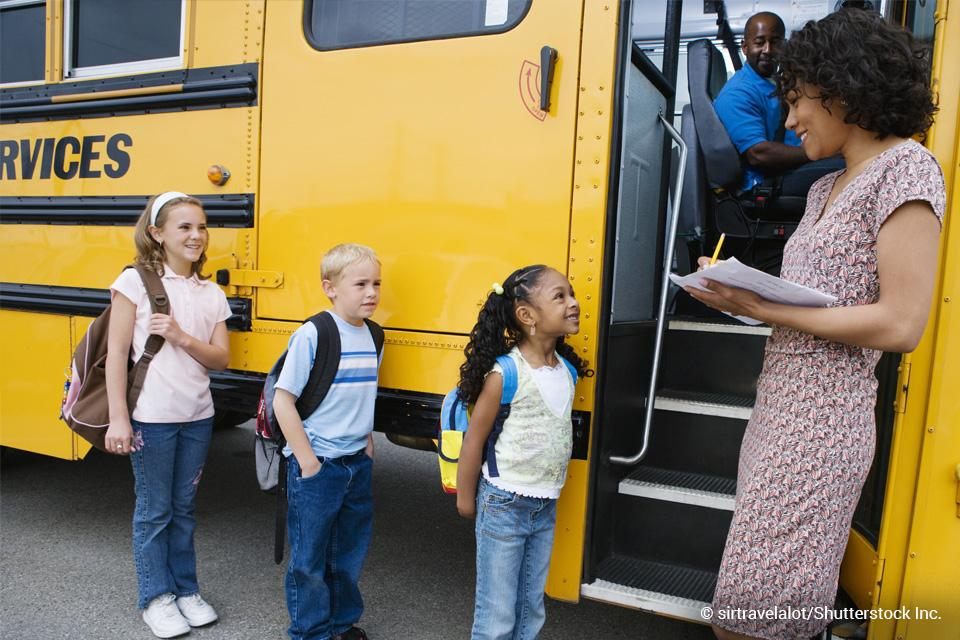 children lined up to get on school bus
