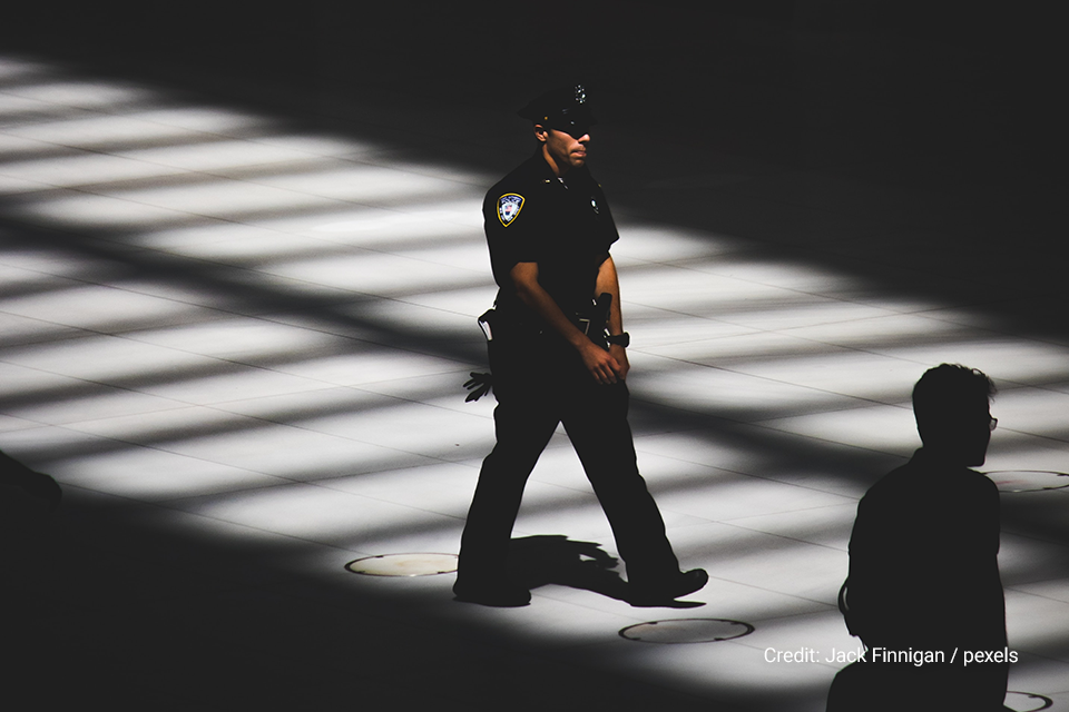 Police officer walking in a darkly lit area in a building.