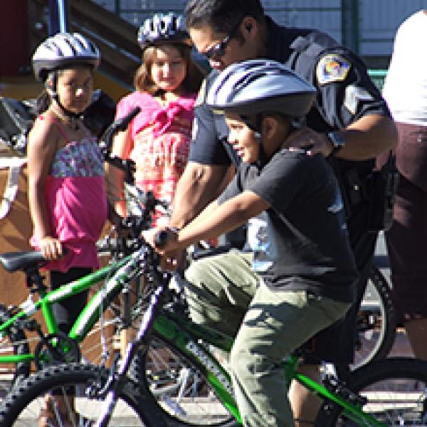 Police officer helps young boy ride a bike.