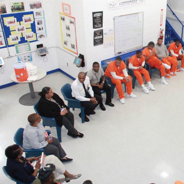 Inmates and program staff seated in a semi-circle